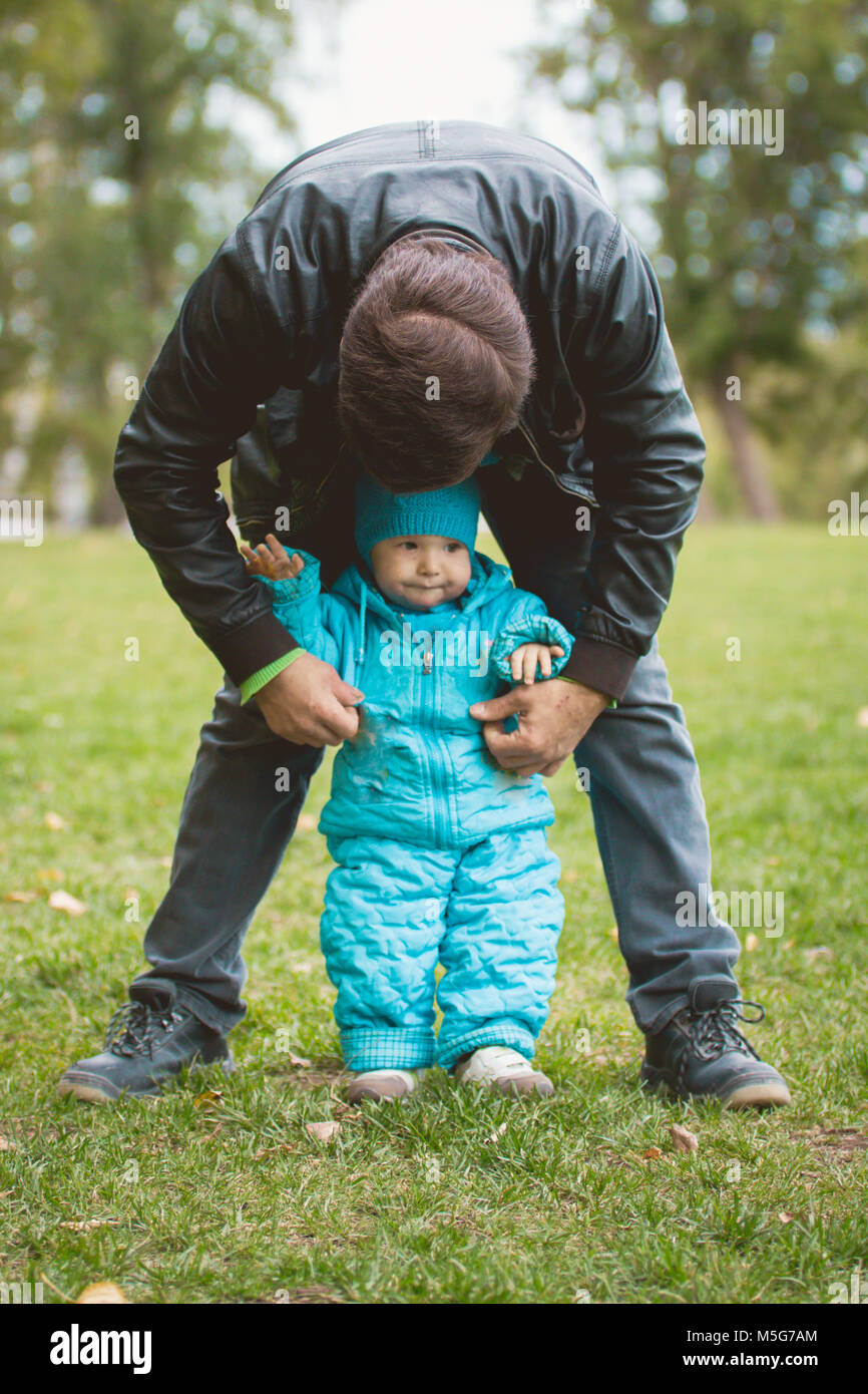 Happy family walking in autumn park: father and his little son - learn to stand independently - Stock Image