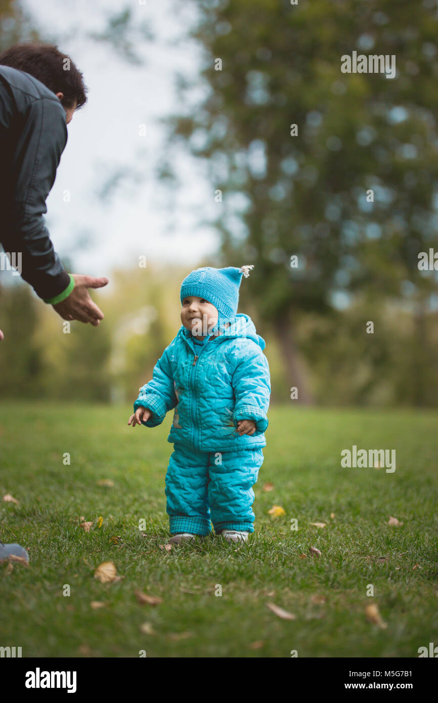 Happy family walking in autumn park: father and his little son - learn to stroll independently - Stock Image