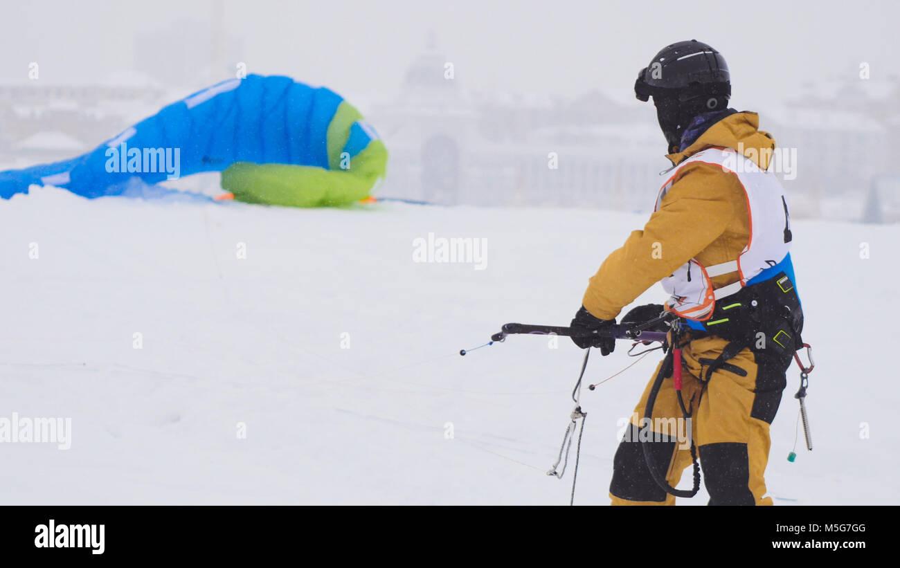 Snowkiting in the snow on frozen river, kite surfer ready for sliding - Stock Image