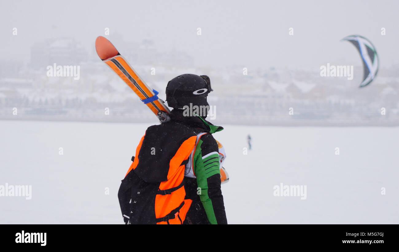 Kite surfer ready for sliding. Snowkiting in the snow on frozen river - Stock Image
