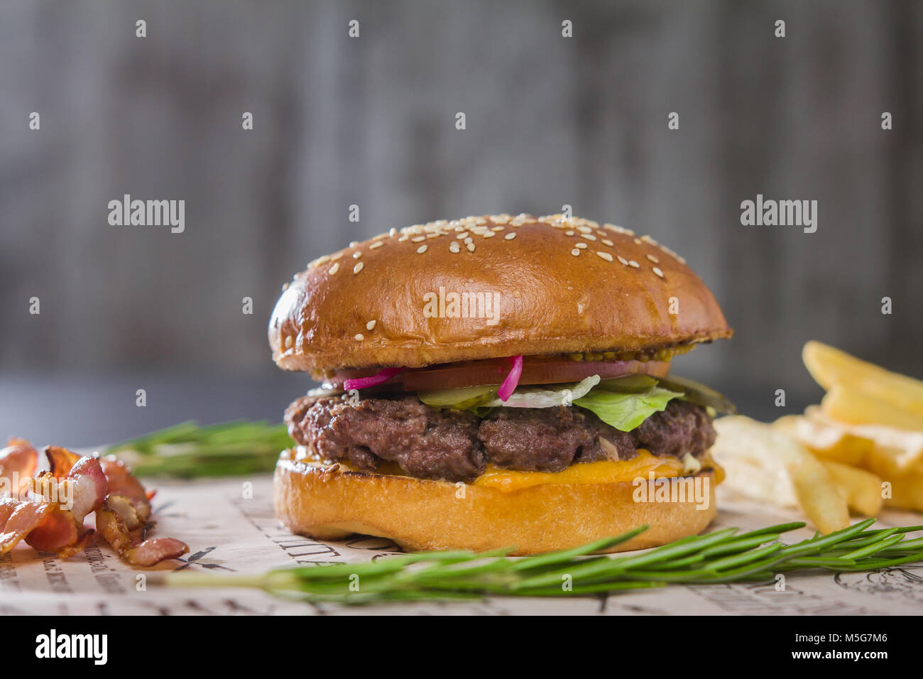 Burger with potatoes on cutting Board, telephoto - Stock Image