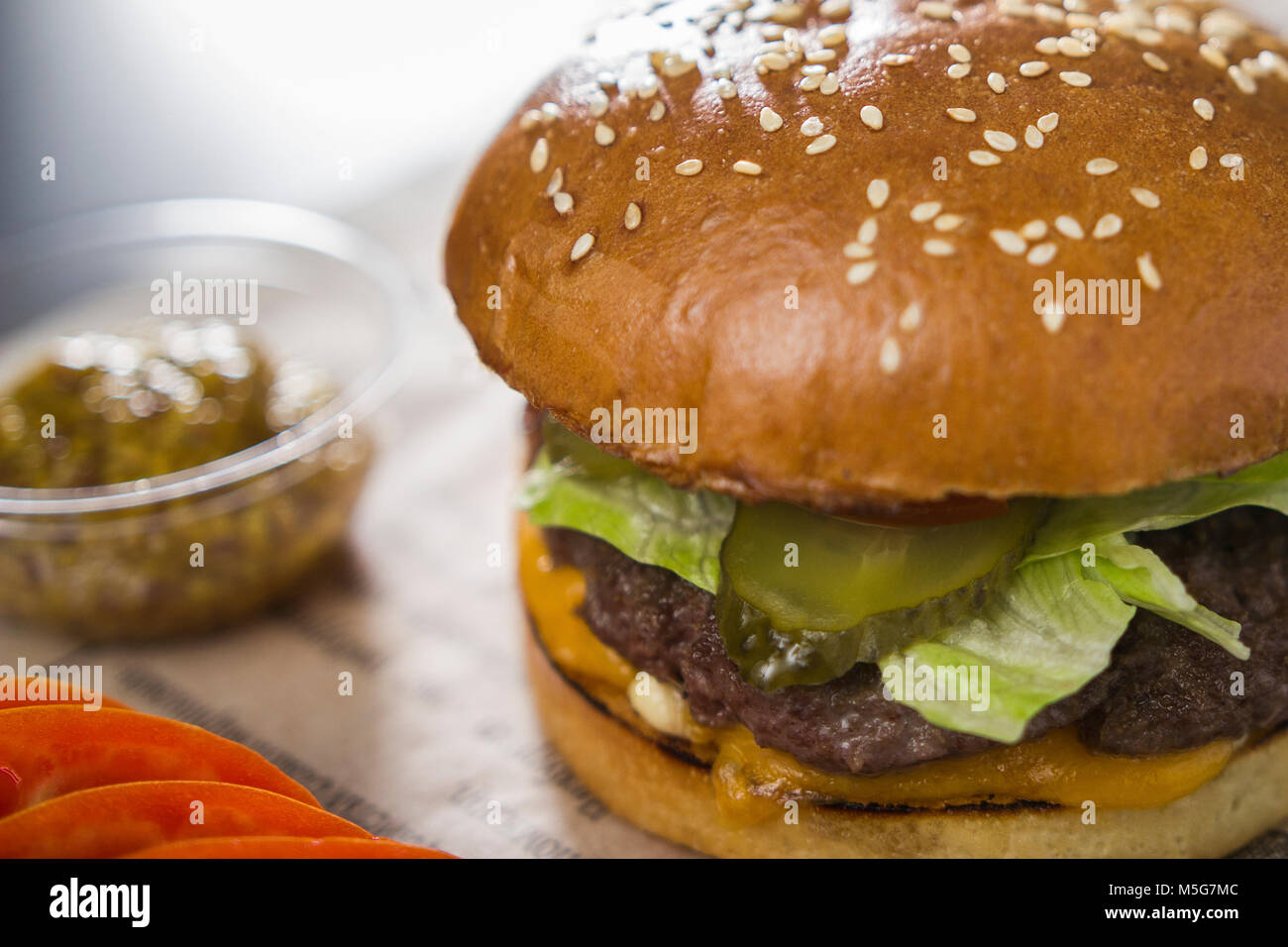 Big tasty burger with mustard on the table - Stock Image