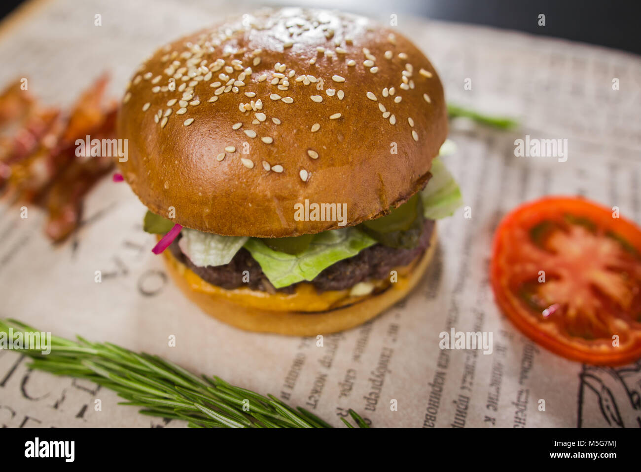 A fresh tasty burger with sliced tomato and bacon - Stock Image