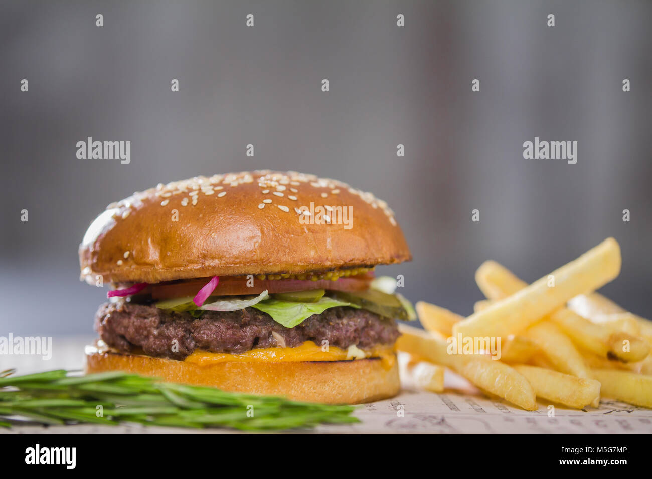 Big fresh appetizing burger with pepper and potatoes - Stock Image