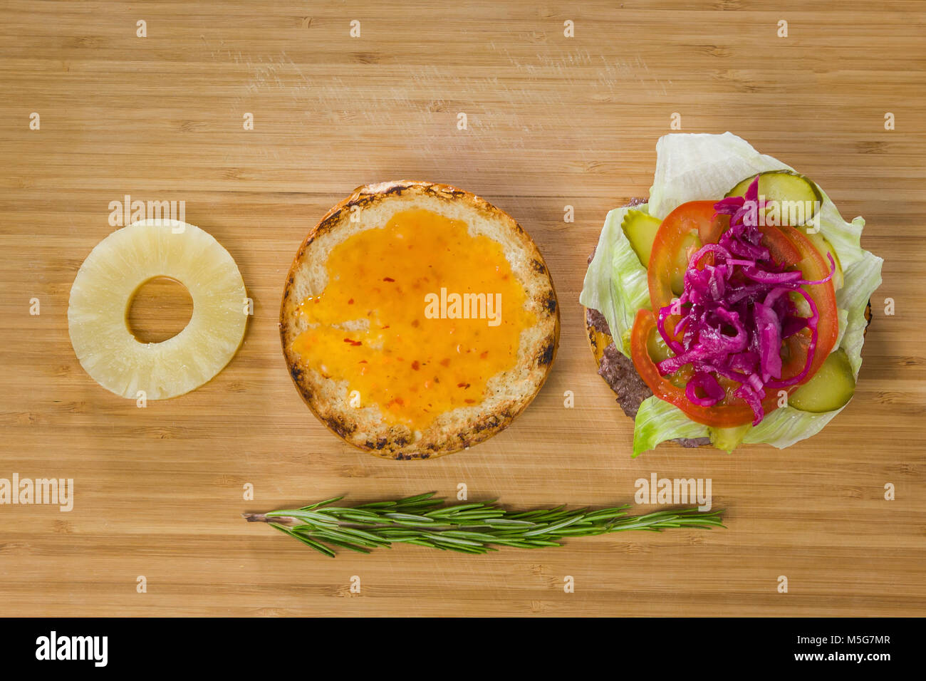 Open burger with pineapple, onion and vegetables - Stock Image