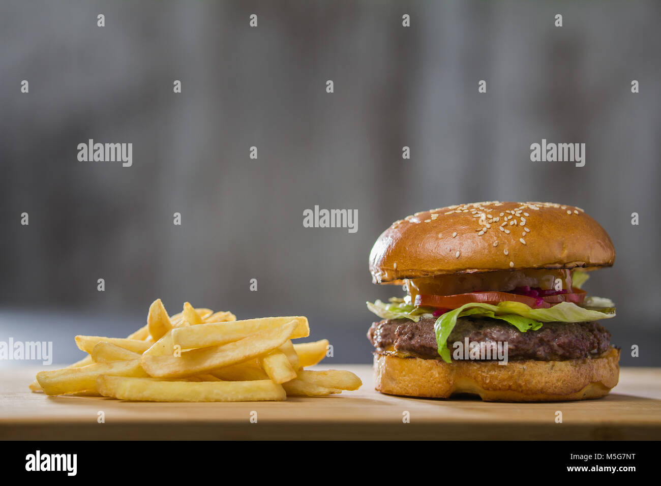 A fresh tasty burger with potatoes on the table - Stock Image