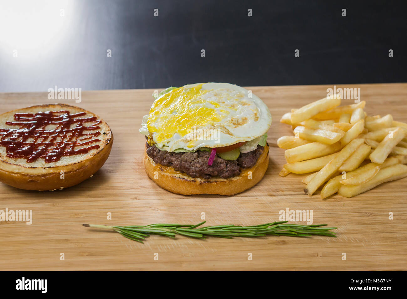 Uncovered tasty burger on the table - Stock Image