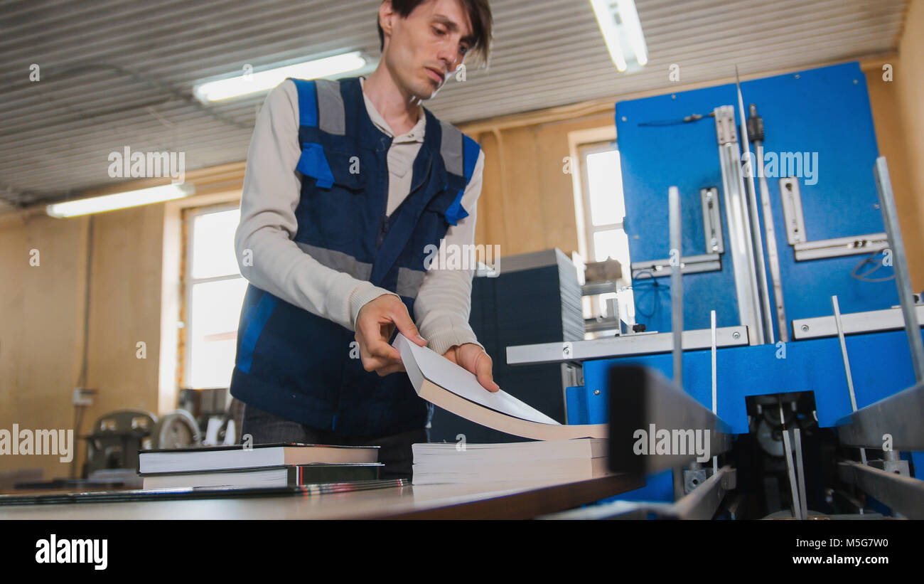 Worker inserts sheets of paper to printing machine, polygraph industry - Stock Image