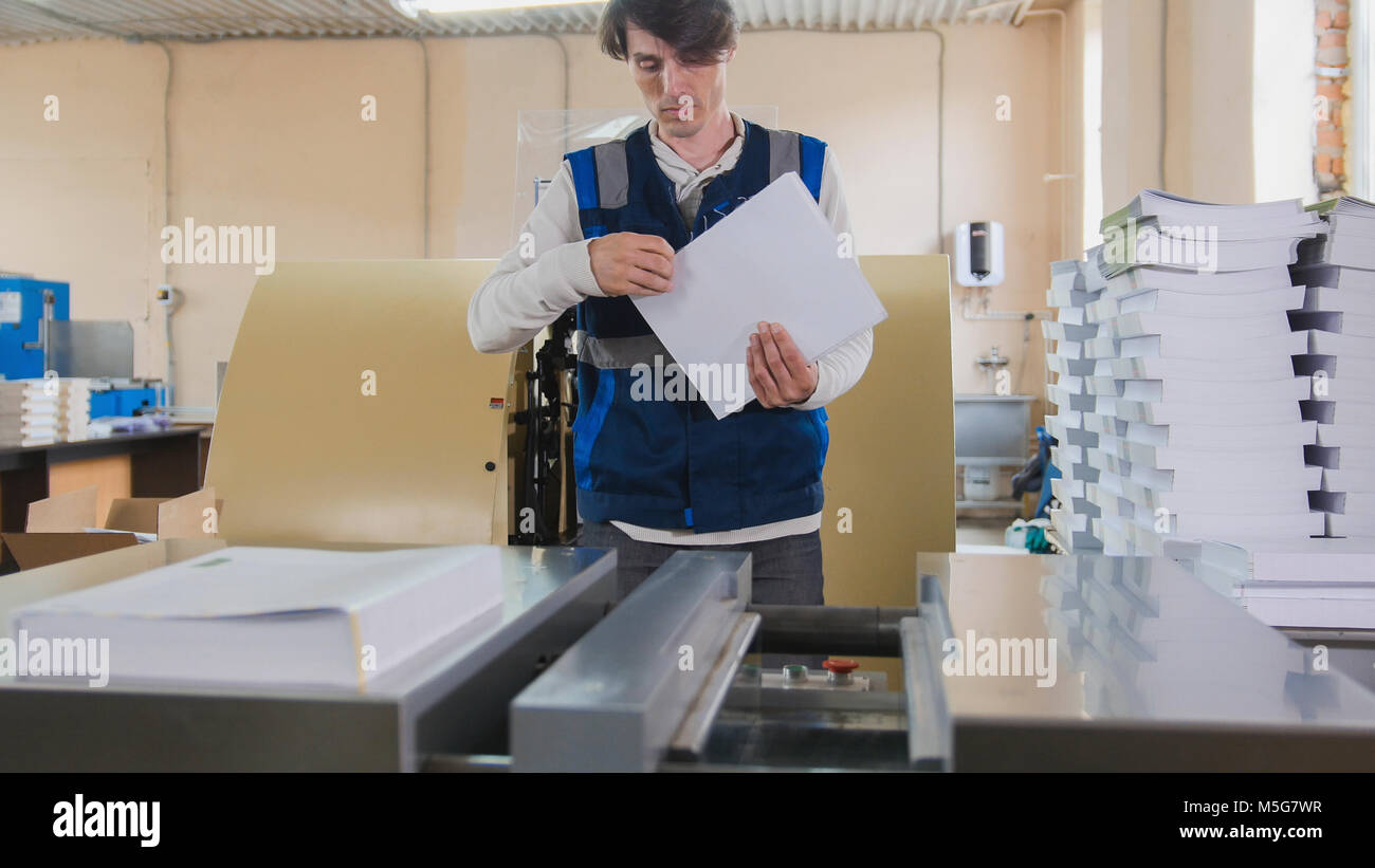Man worker near printing machine, polygraph industry - Stock Image