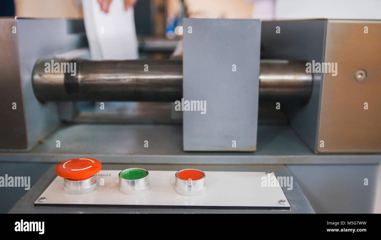 Red button on control panel of folding machine - printing polygraph industry, close up - Stock Image