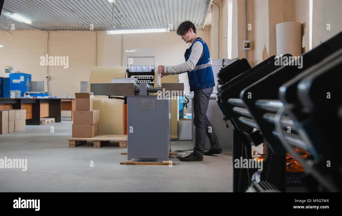 Worker and printing machine, polygraph industry - Stock Image