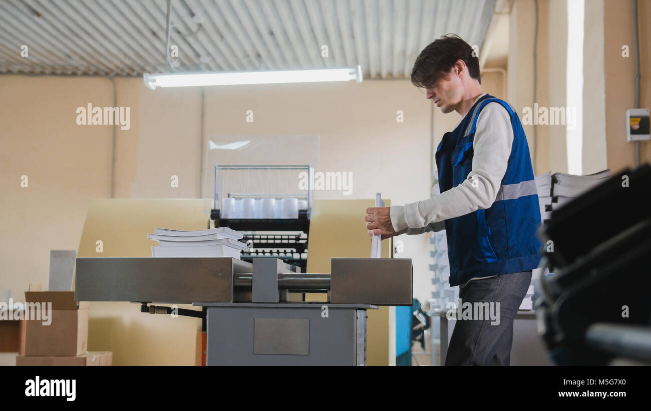 Worker and printing machine, polygraph industry - close up - Stock Image
