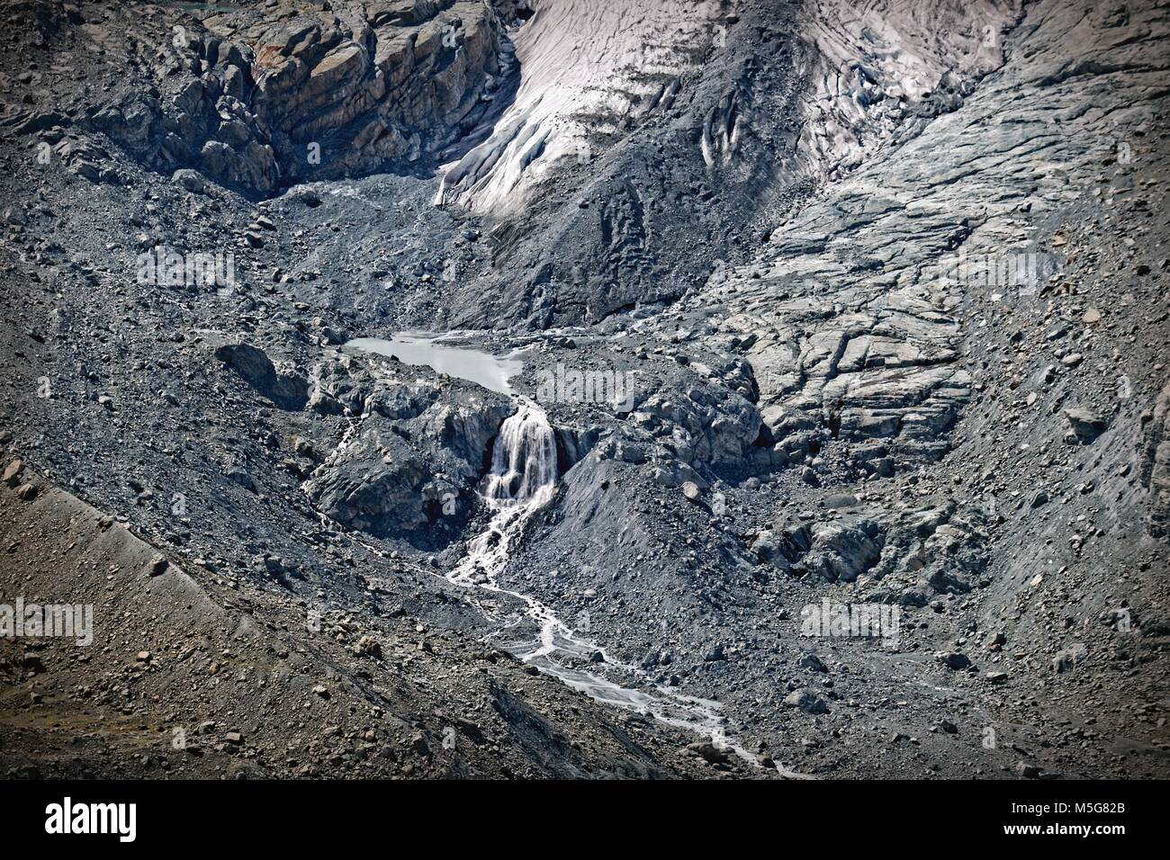 Streams feeding into and out of lake in floor of glacial valley, with glacier snout, and moraine - Stock Image
