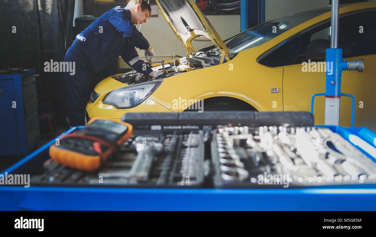 Car auto electronics - mechanic repairs a car - unscrews detail of automobile - garage service - Stock Image