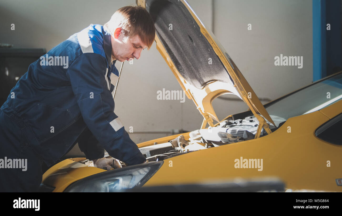 Mechanic in car workshop - repairing in engine compartment - Stock Image