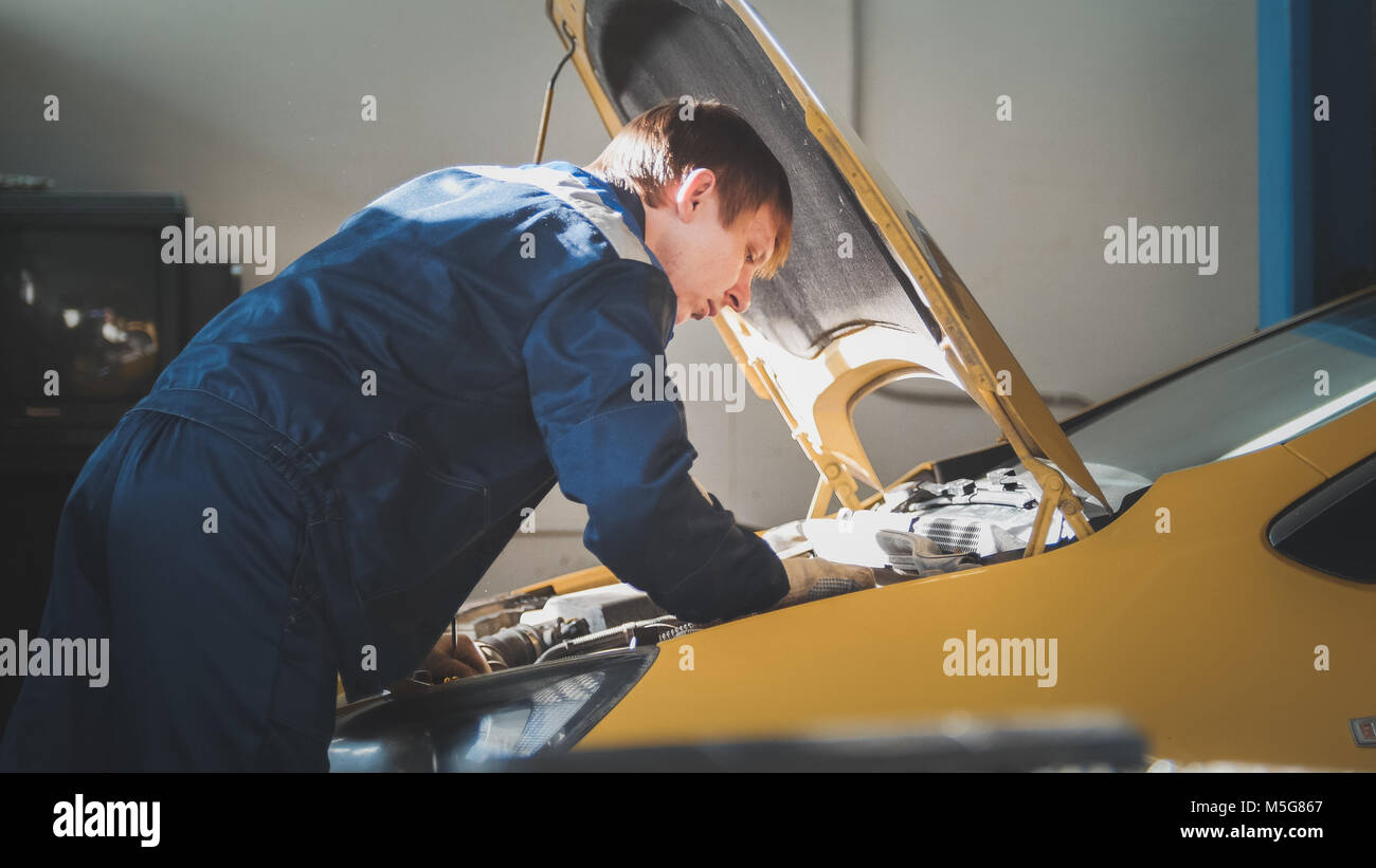 A mechanic checks the electrical in the hood of the yellow car- repairing in engine compartment - Stock Image