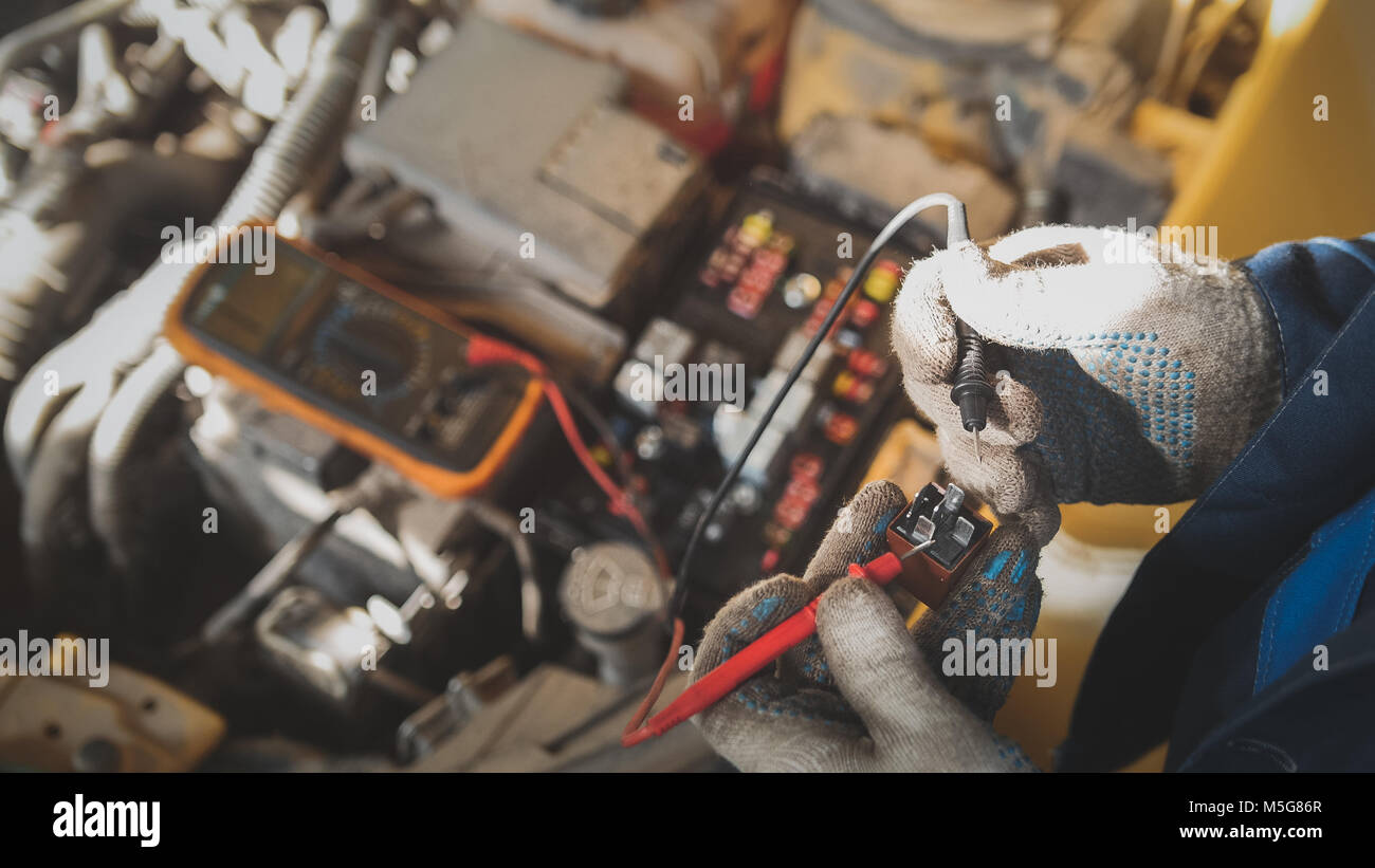 Mechanic works with car electrics - electrical wiring, voltmeter - Stock Image
