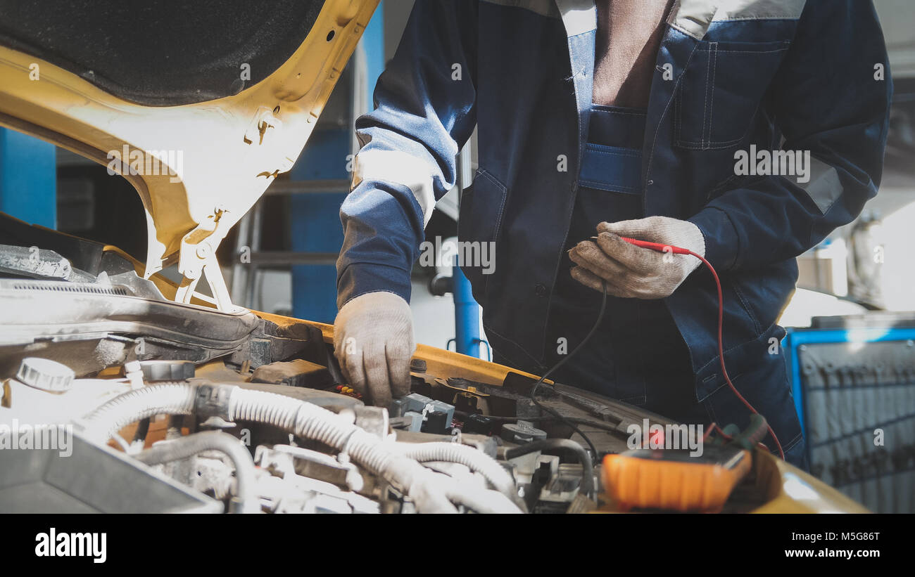 Mechanic in car workshop works with car electrics - electrical Stock ...