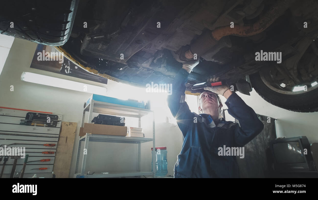 Mechanical auto workshop - a mechanic checks the suspension of car, wide angle - Stock Image