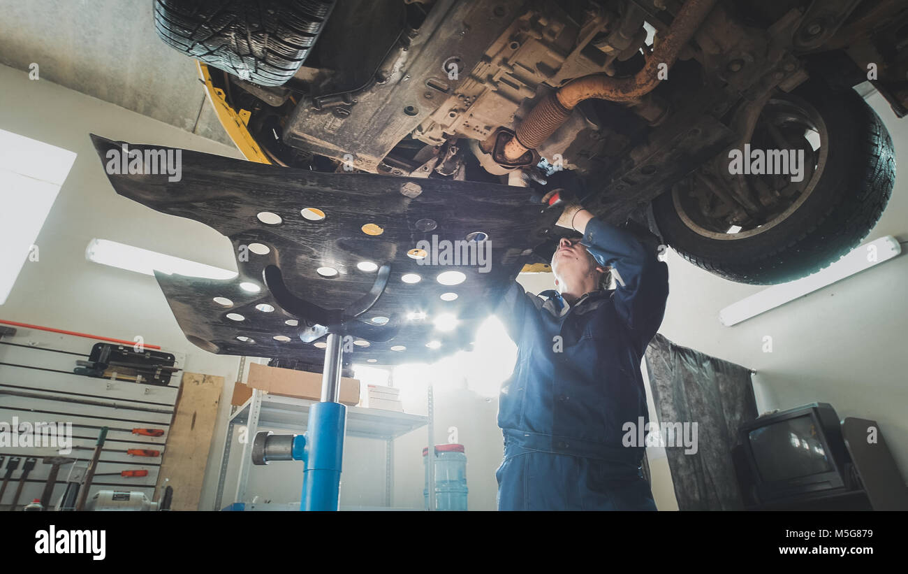 Car automobile service - mechanic checks the bottom of car - Stock Image