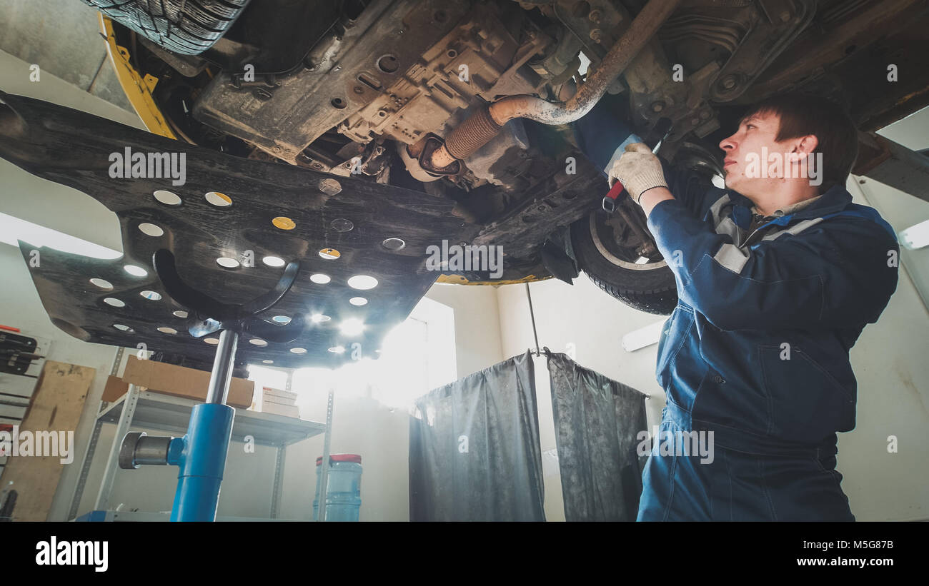 Car automobile service - worker mechanic checks the bottom of car - Stock Image
