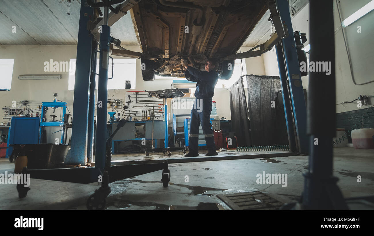 Garage mechanical workshop - mechanic checks bottom of car - lifted auto standing in automobile service - Stock Image
