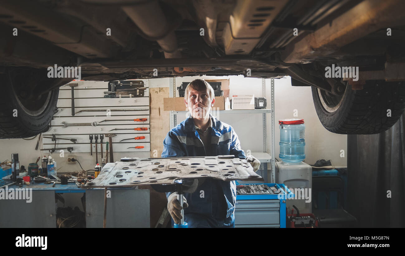 Mechanic in automobile garage repairing workshop - under lifted car - Stock Image