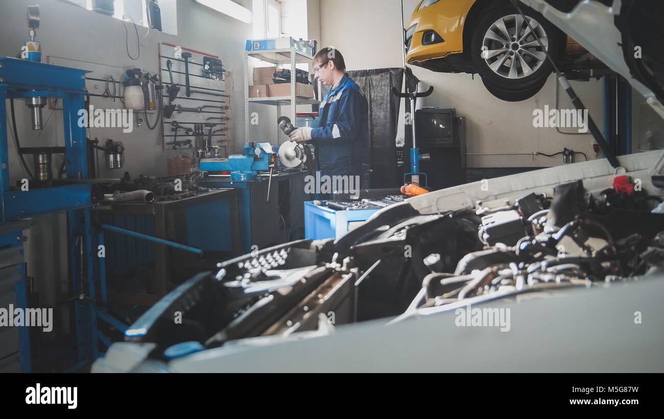 Mechanic in the garage, car preparing for professional diagnostics - Stock Image