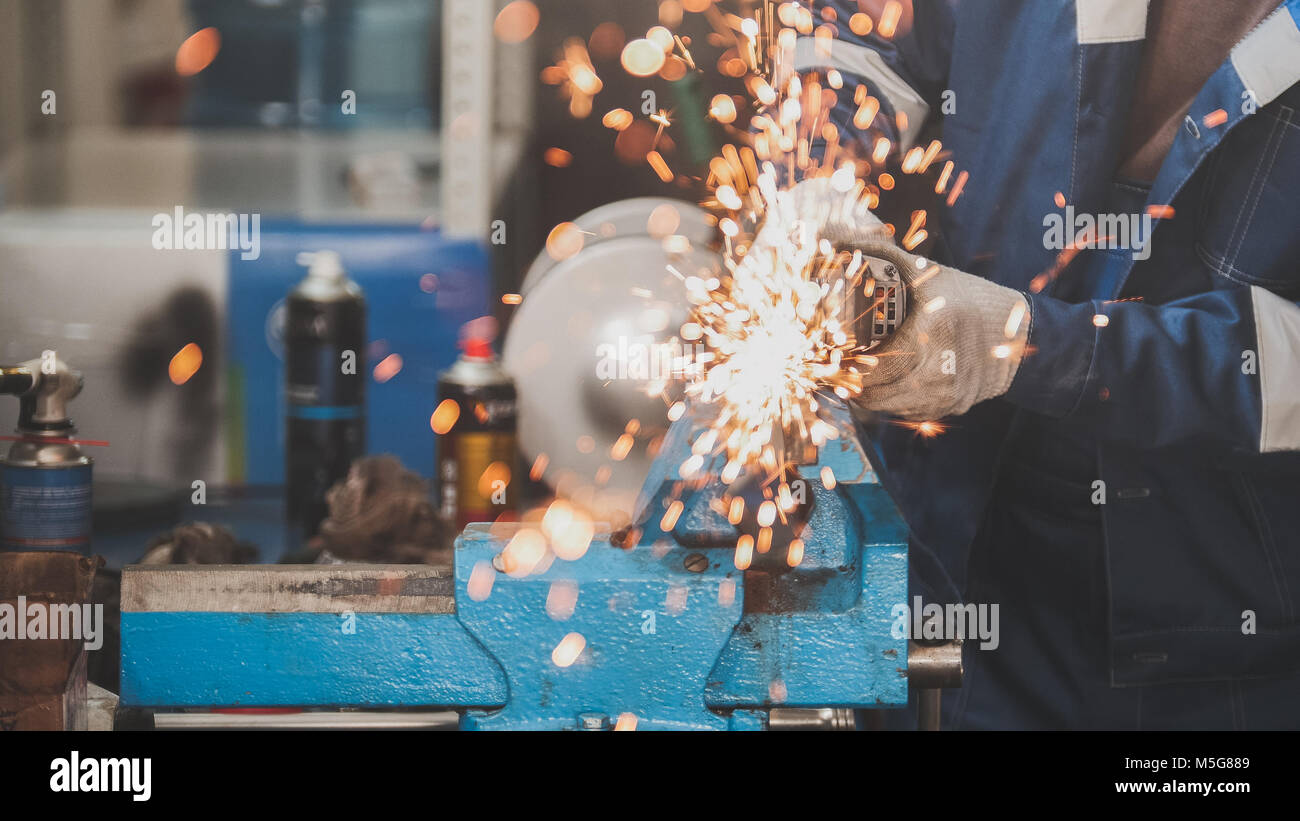 Car service - worker grinding metal construction with a circular saw Stock Photo