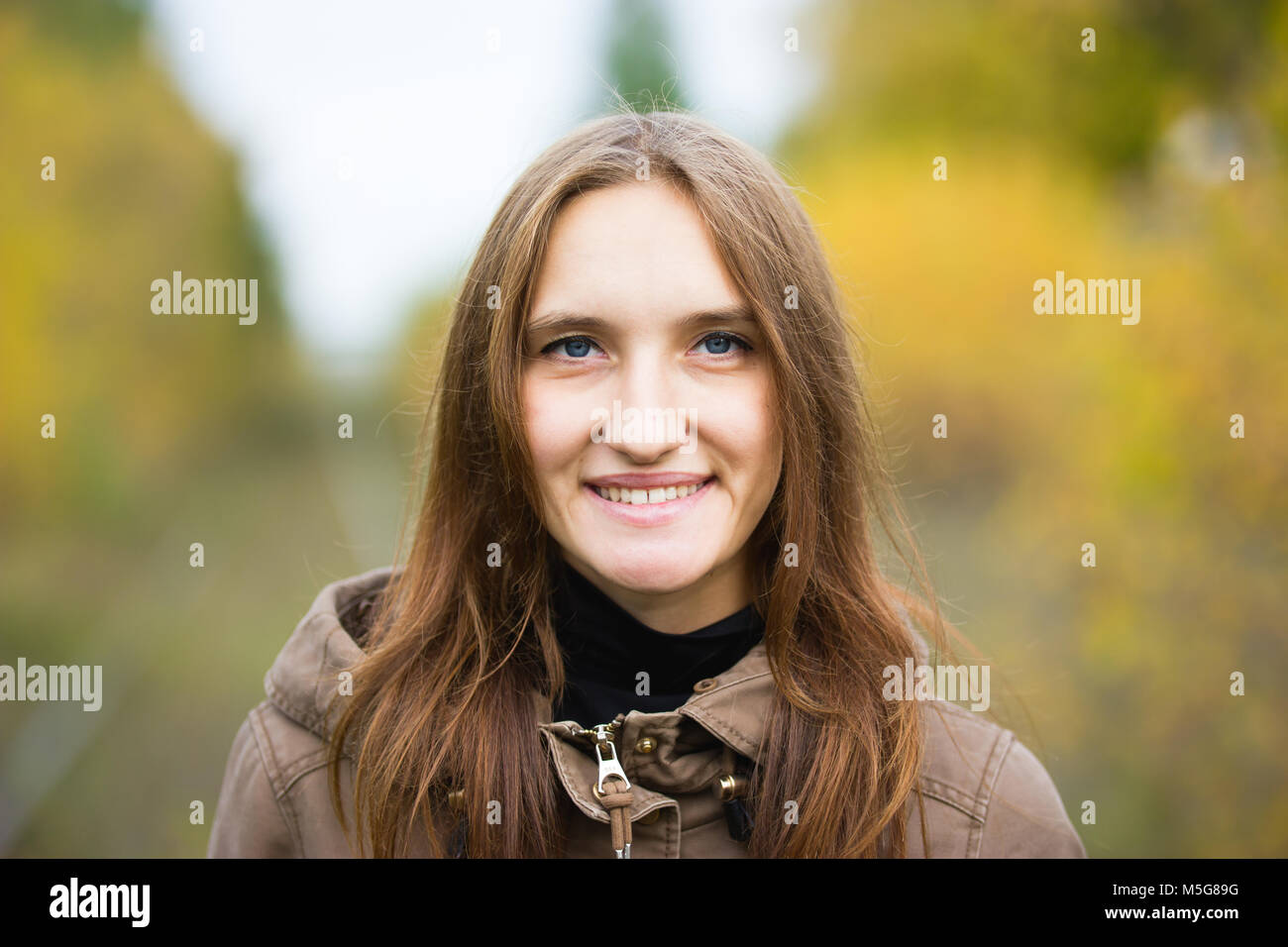 Portrait of young cute woman in fall autumn park. Beautiful caucasian girl walking in forest, close up - Stock Image