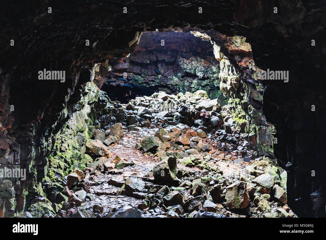 A hike through a lava cave in iceland tunnels are very narrow and partially blocked - Stock Image