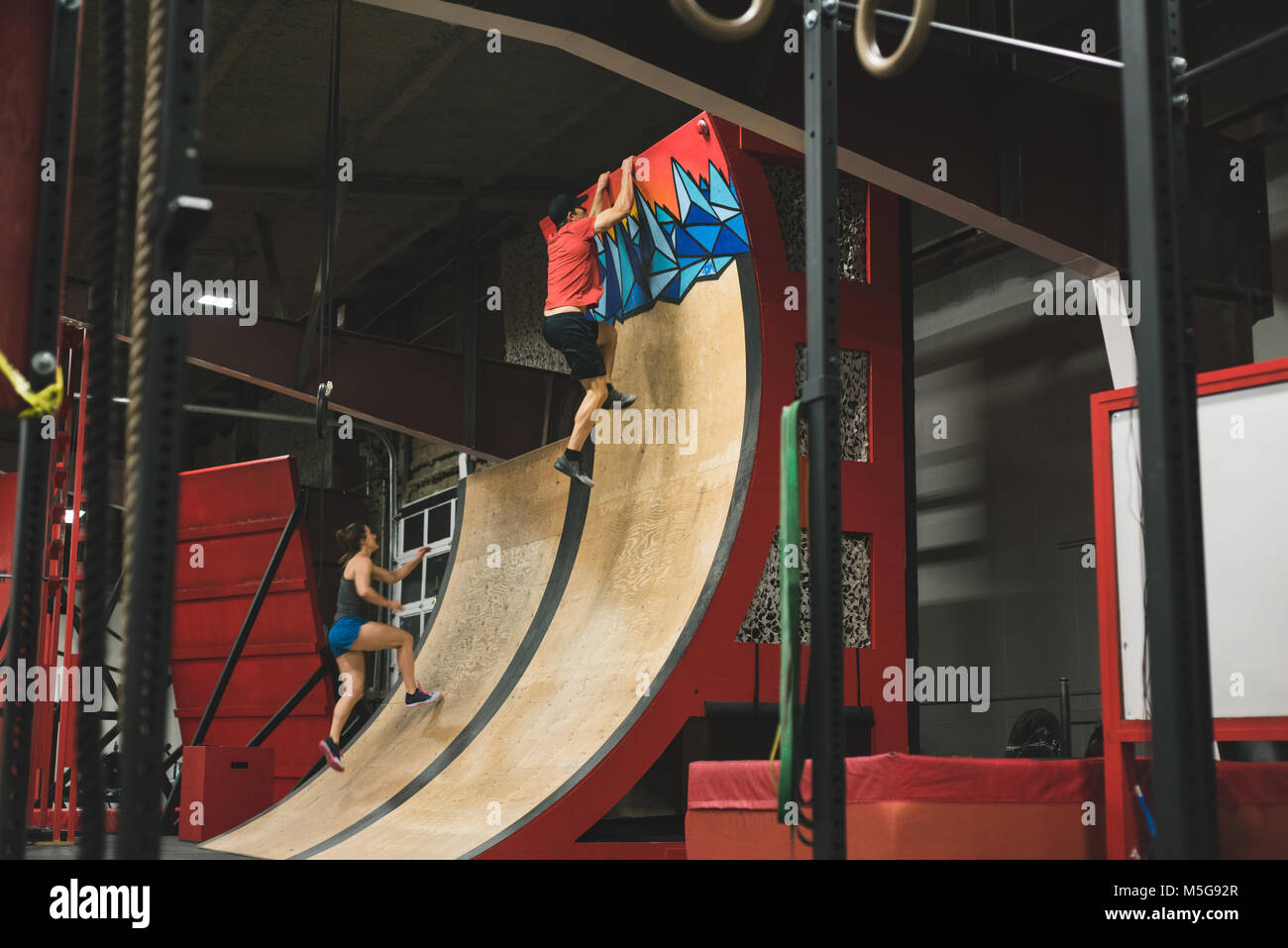Muscular couple climbing a warped wall Stock Photo
