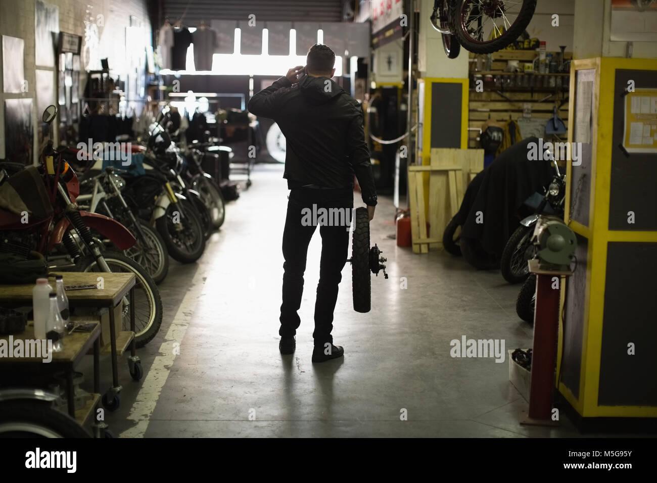 Mechanic holding tyre in garage - Stock Image