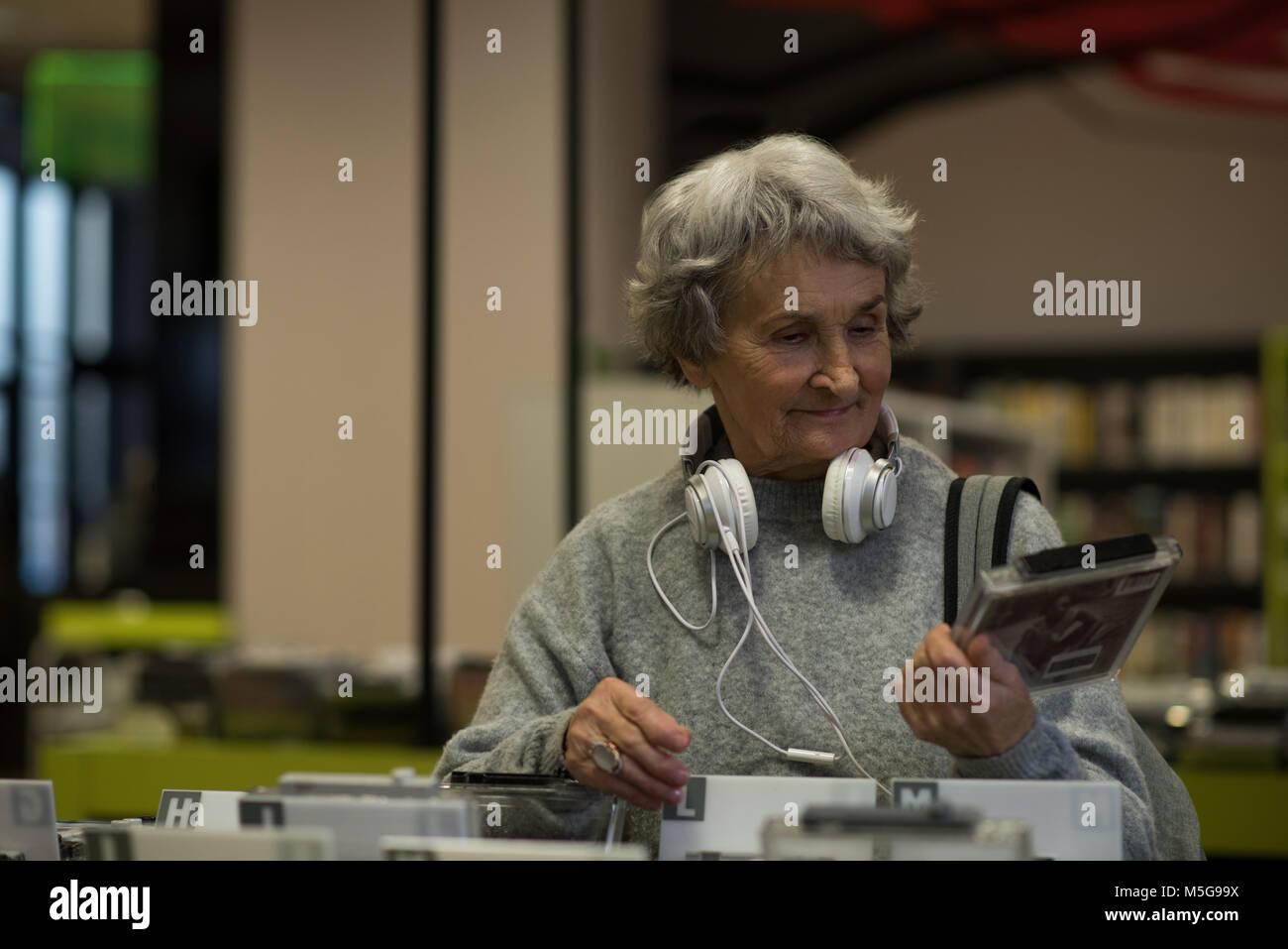 Senior woman choosing a dvd cassette - Stock Image