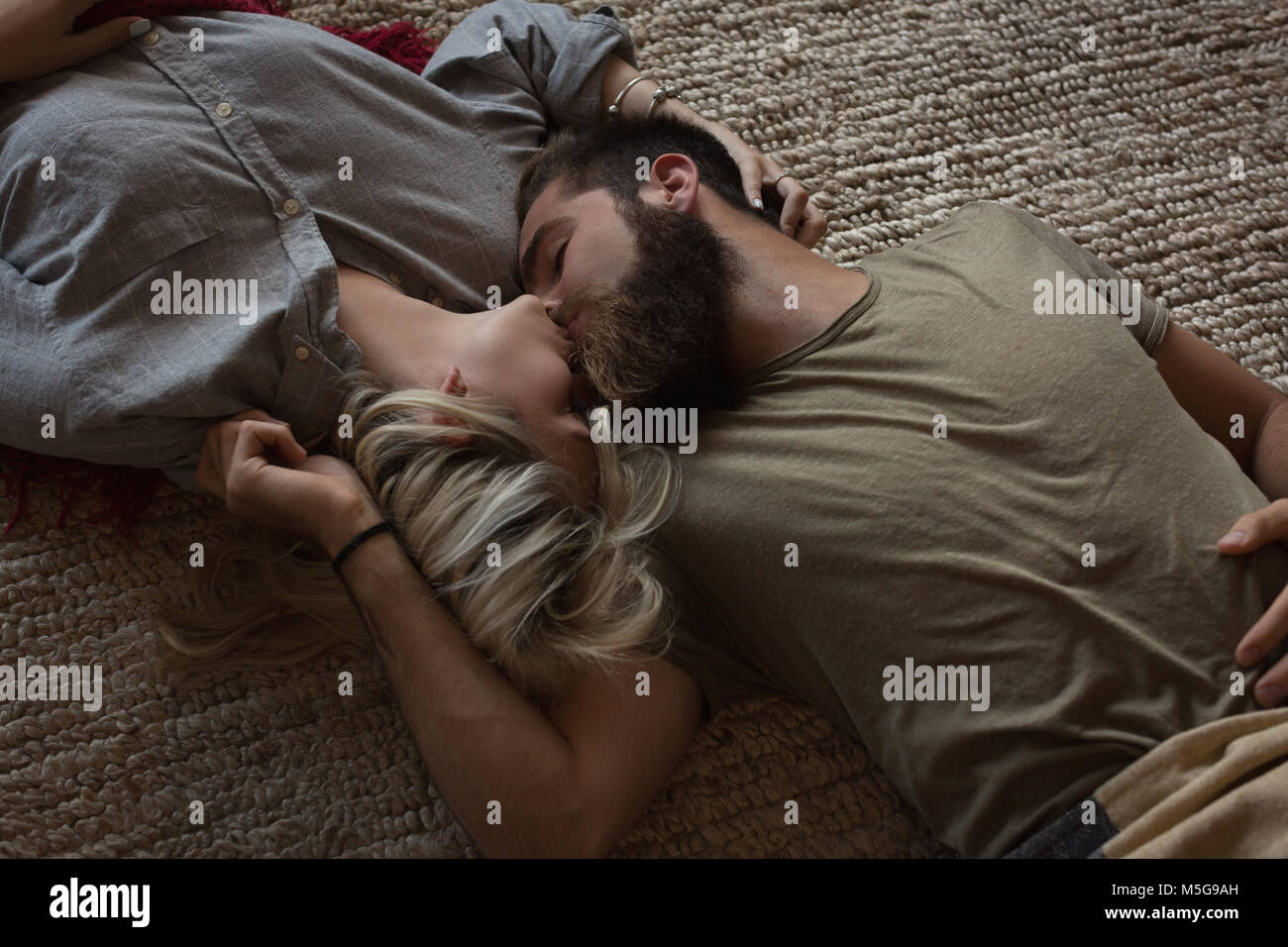 Couple kissing each other while lying in living room - Stock Image