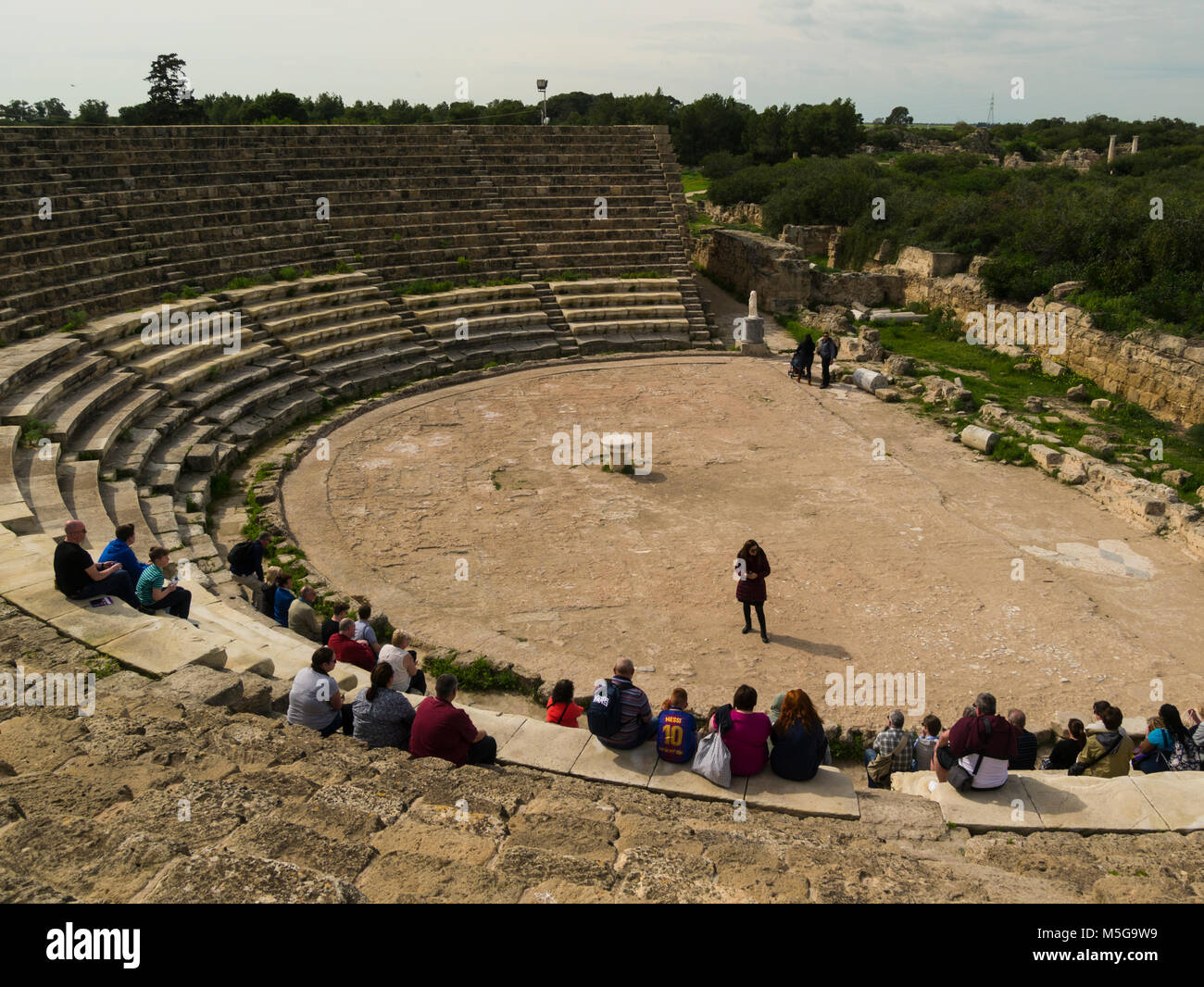 Tourists sitting in ruins of Theatre with 50 rows seating 15000 people in Salamis Famagusta Turkish Republic of - Stock Image