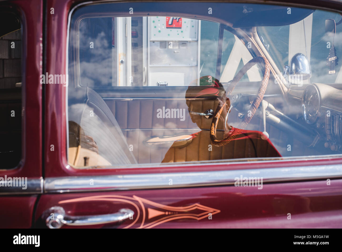 The reflection of a man in the window of a vintage Chevy car. - Stock Image