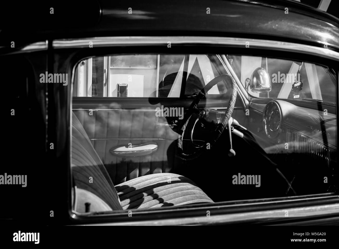 The monochrome  reflection of a man in a vintage Chevy car. - Stock Image