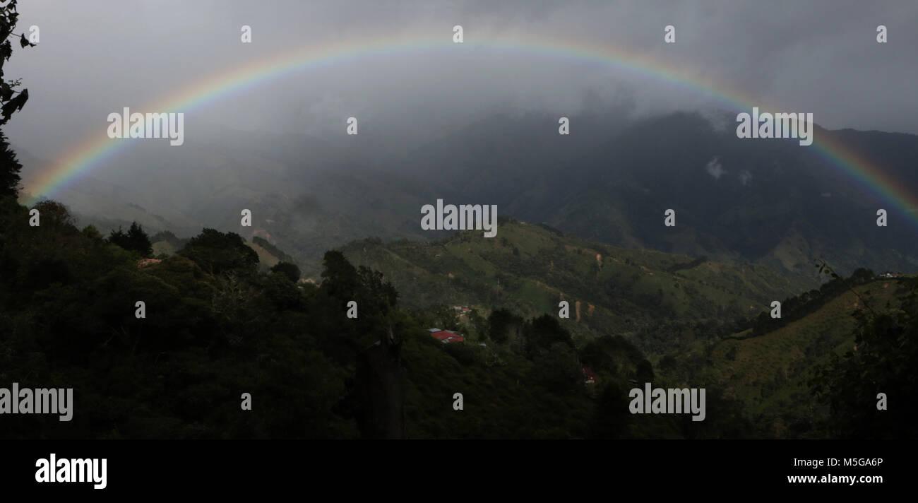 Rainbow over hills farmland Costa Rica Stock Photo