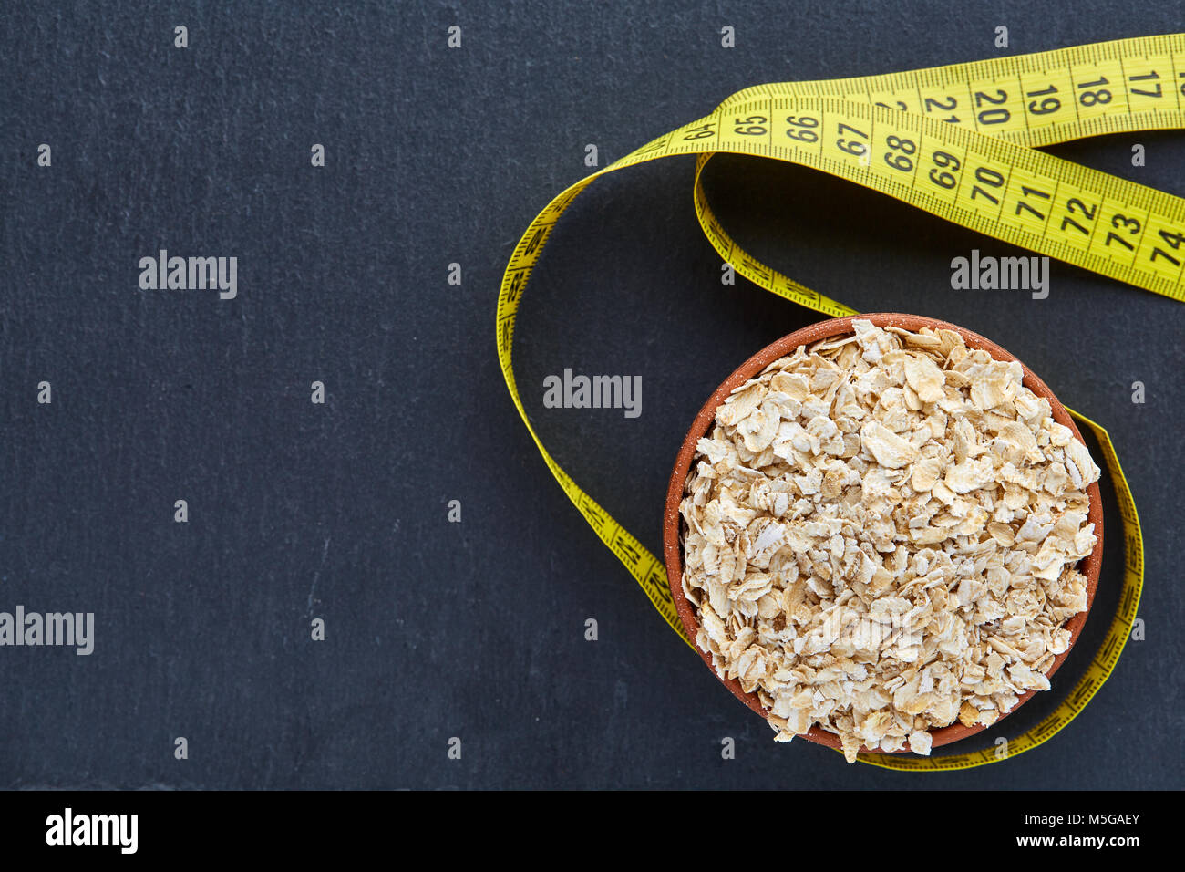 Top view close-up picture of a ceramic clay dark brown bowl of oatmeal hugged with long yellow flexible ruler isolated - Stock Image