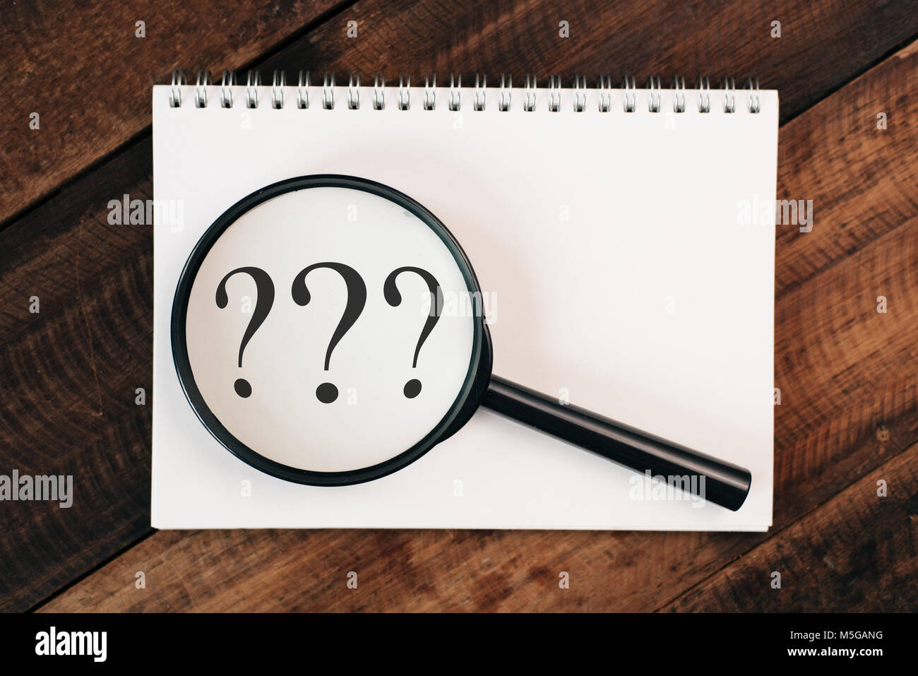 magnifying glass zooming into question mark on notebook on a wooden table. problem and research concept Stock Photo