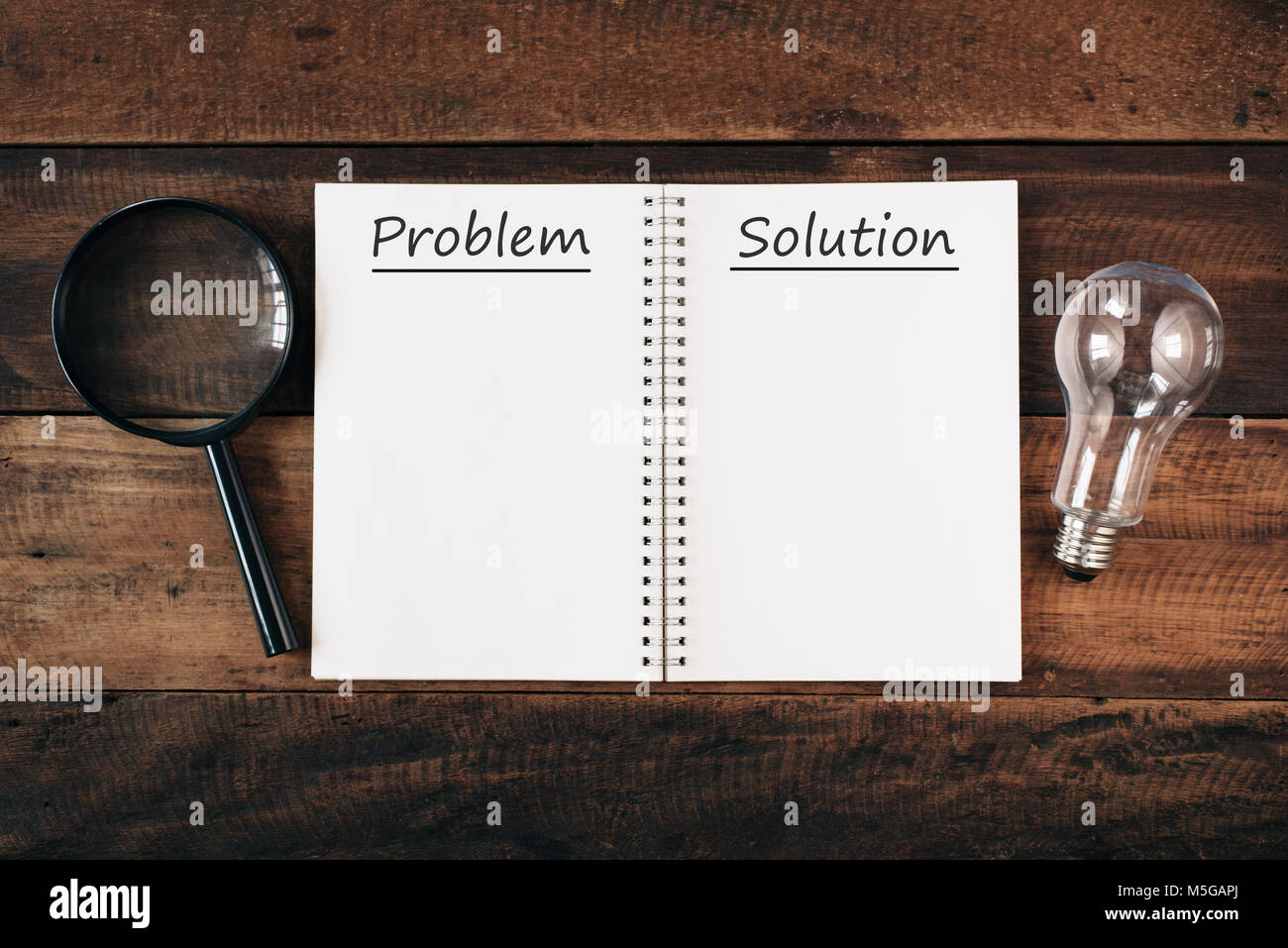 magnifying glass, bulb and notebook written PROBLEM and SOLUTION with copy space on wooden table. problem solving - Stock Image