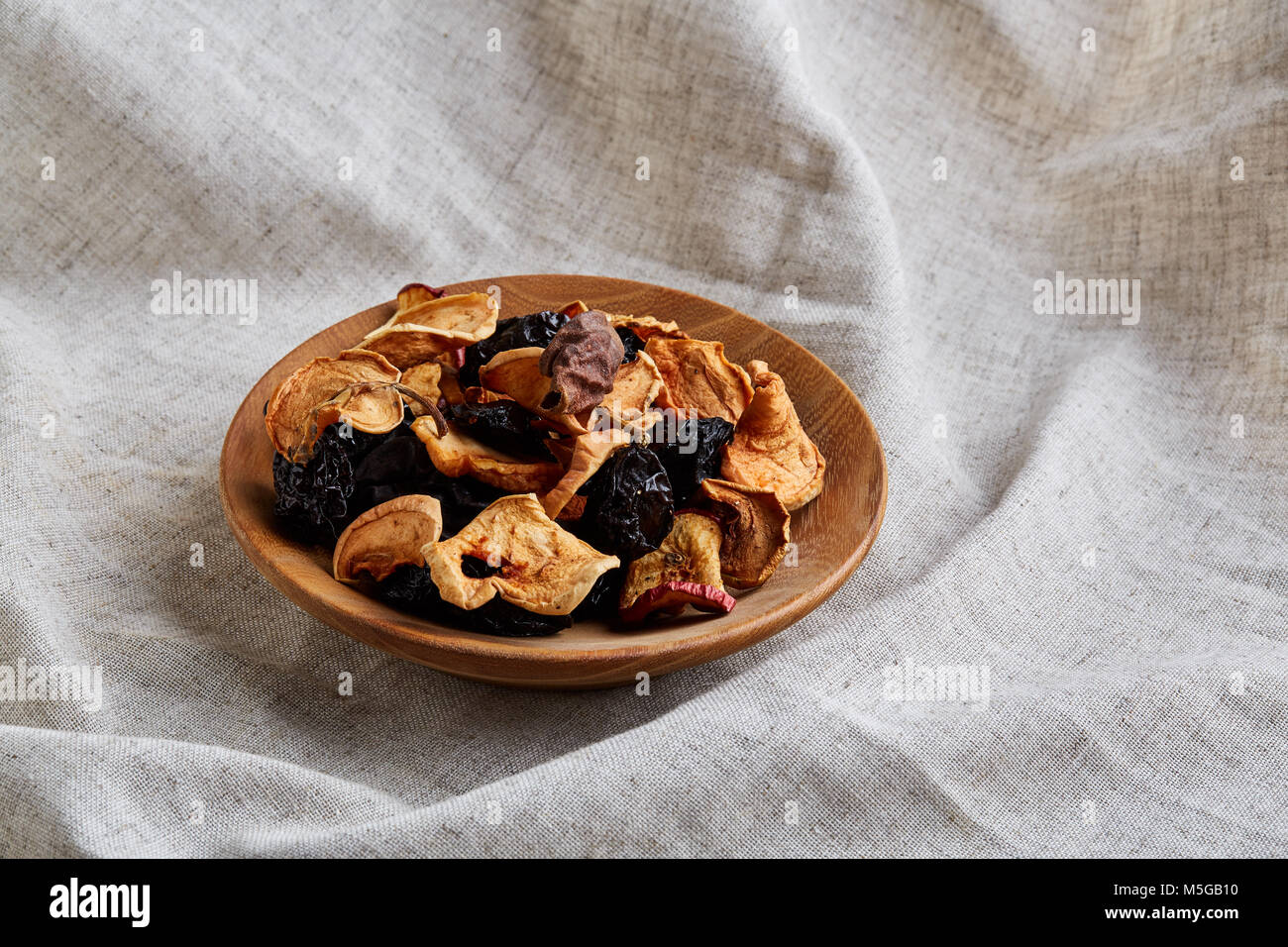 Wooden Plate With Dried Fruits On A Light Grey Cotton Tablecloth Or Napkin,  Close Up. Nutritious And Tasty Snack. Healthy Lifestyle Concept.