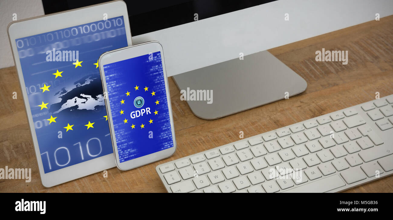 Composite image of various electronic gadgets on table - Stock Image
