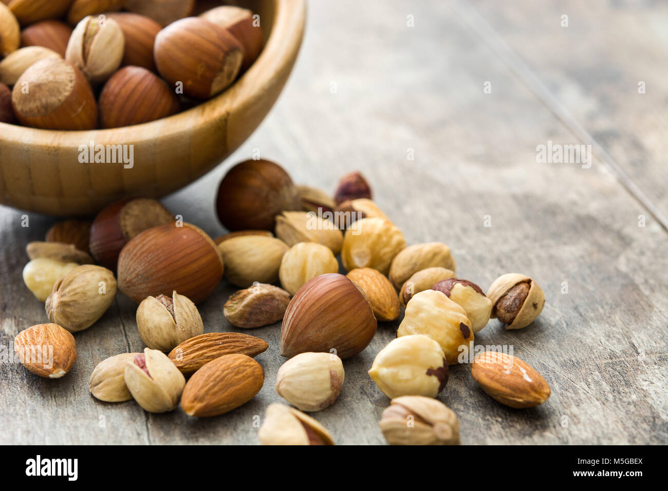 Assorted mixed nuts in bowl on wooden table - Stock Image