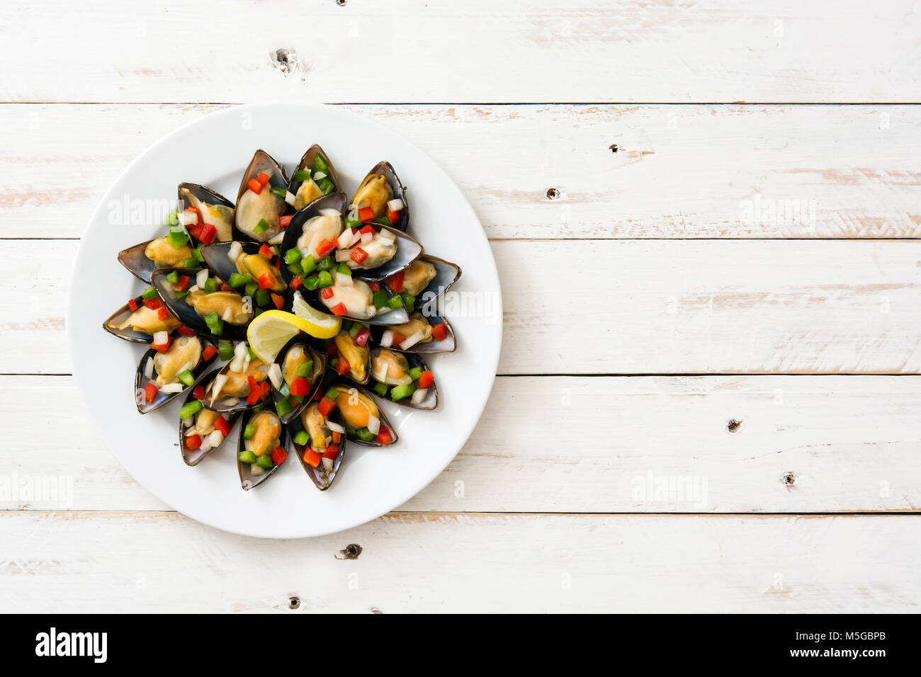 Steamed mussels with peppers and onion on white wooden table Stock Photo