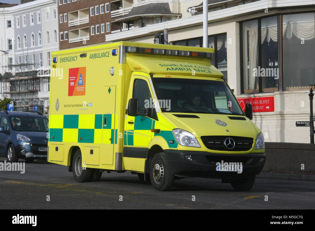 A FRONT OFFSIDE SUNNY VIEW OF A SOUTH EAST COAST AMBULANCE