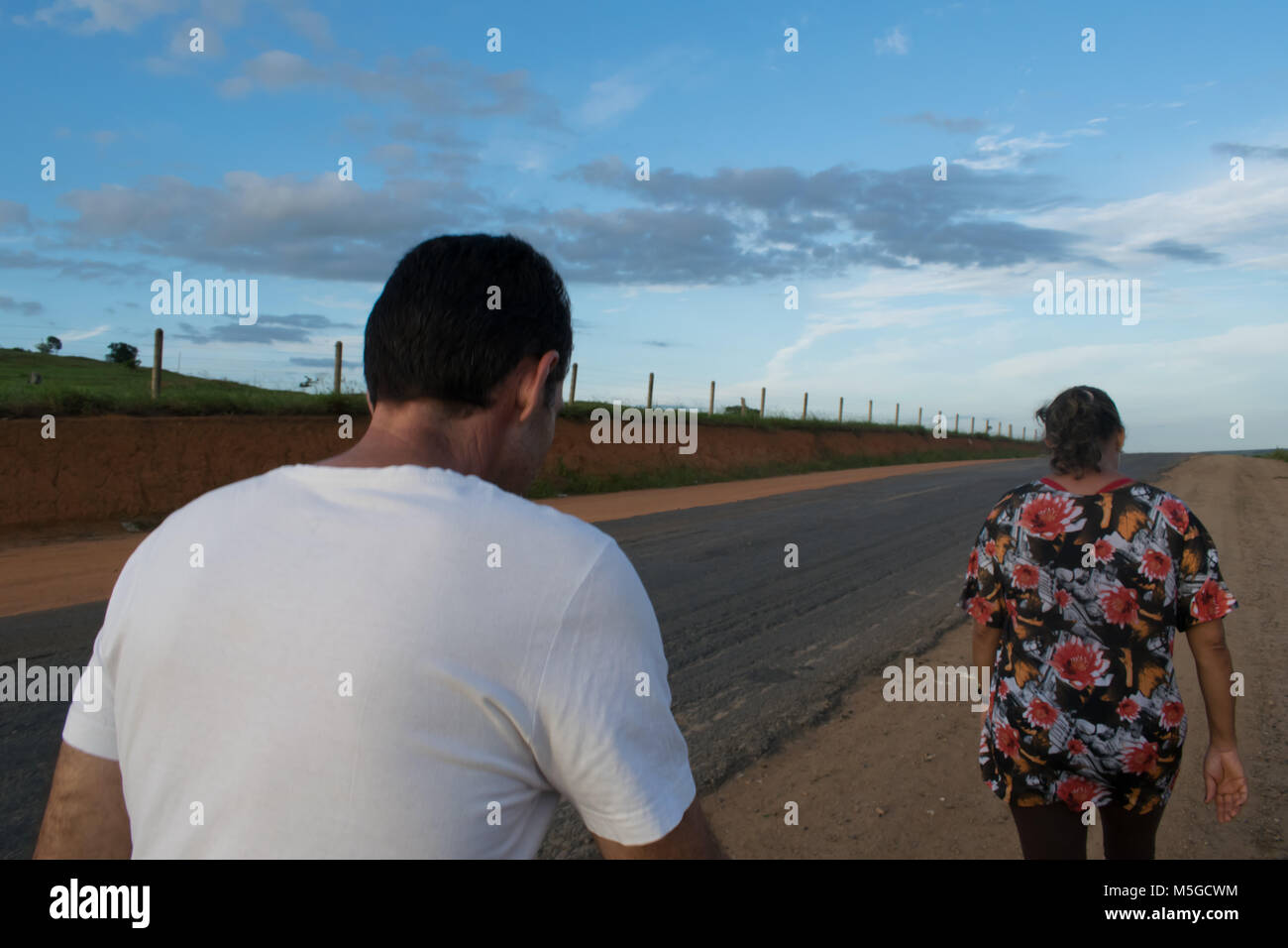 A man and a woman walking alone on the road - Stock Image