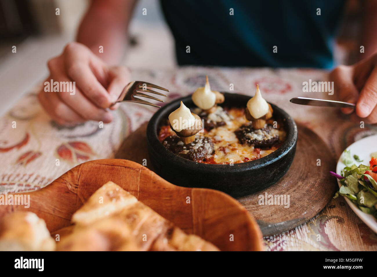 Man's hands holding cutlery - preparing to eat dish with mushrooms at table in cafe - Stock Image