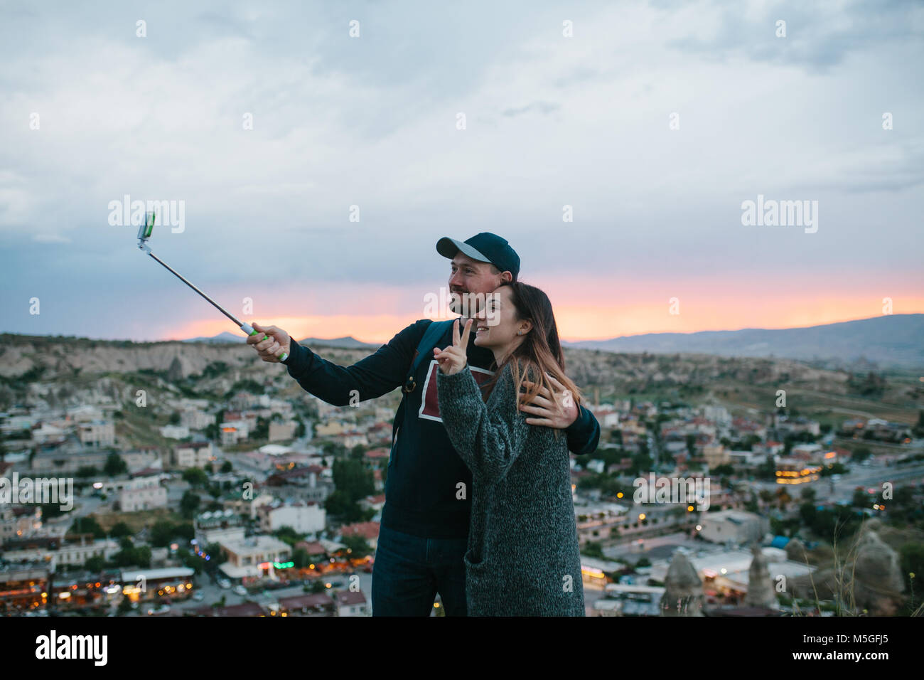 A beautiful couple doing selfie at sunset against the backdrop of the city of Goreme in Cappadocia in Turkey. - Stock Image